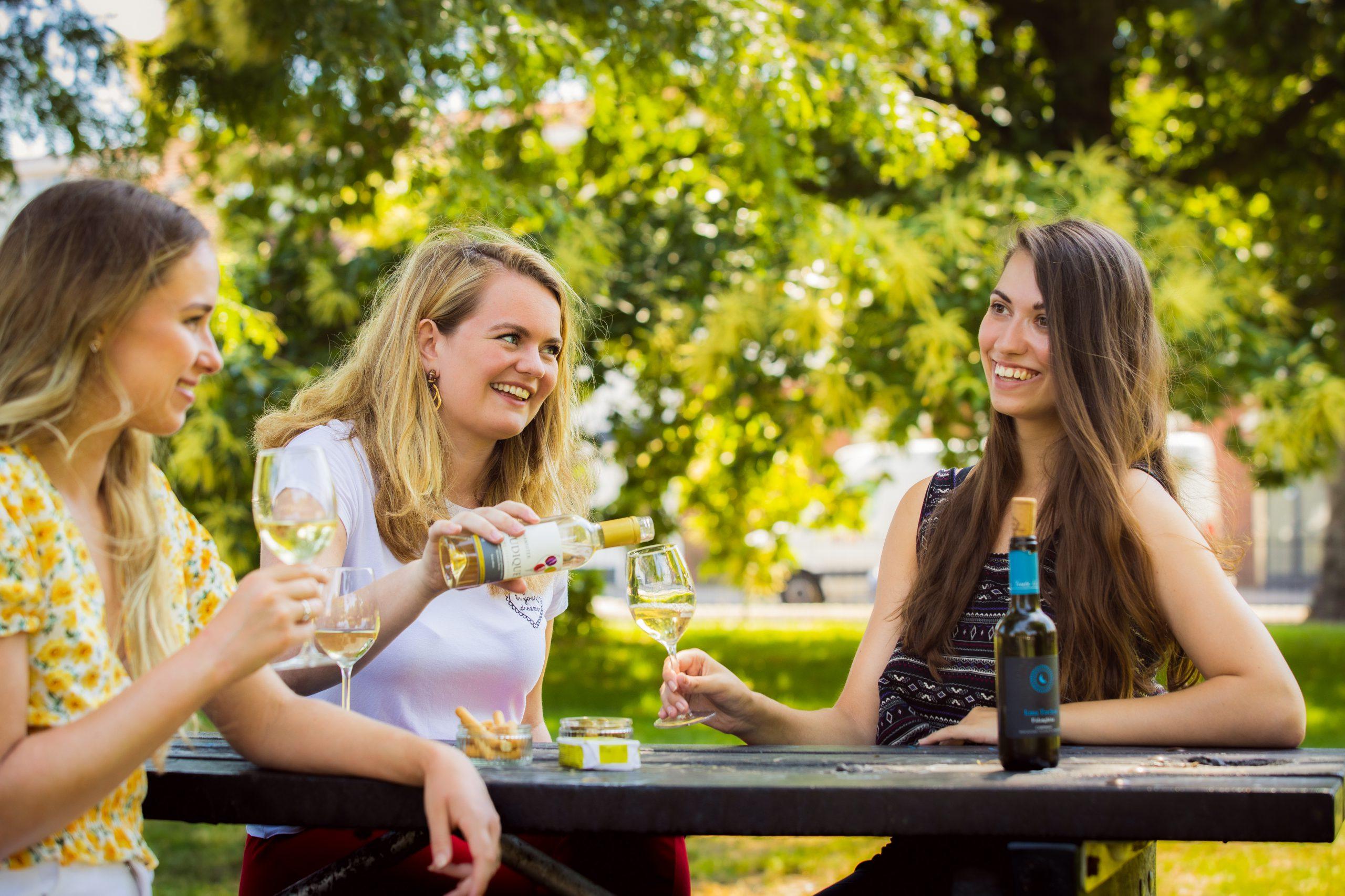 vrouwen wijndrinken groen picnic tafel